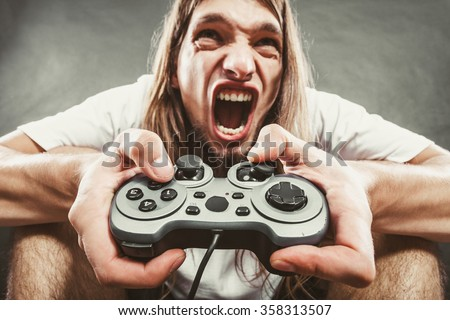 Addiction. Stressed depressed young man playing gaming on pad. Angry guy with controller pad play console. Face expression. - stock photo