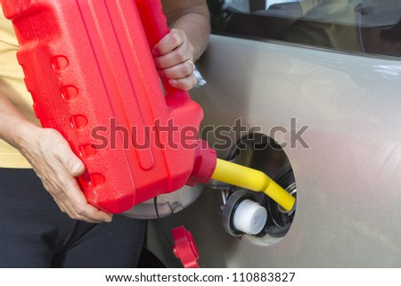 Adding fuel in car with Red Plastic Gas can (fuel container)-closeup - stock photo