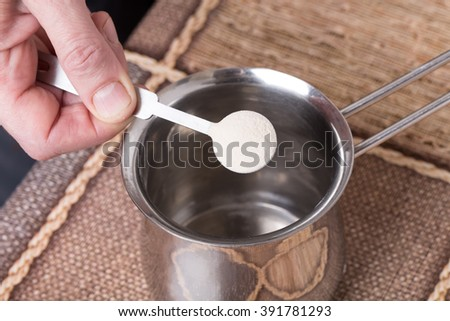 Adding powdered gelatin to water in metal pot. Macro. Photo can be used as a whole background. - stock photo