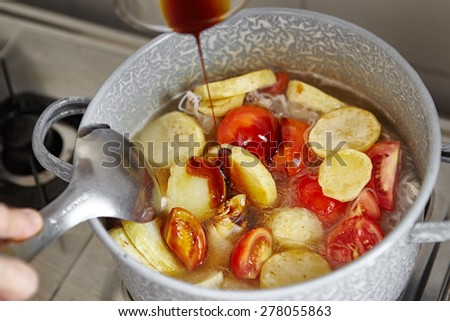 Adding sauce the cooking in the pan - stock photo