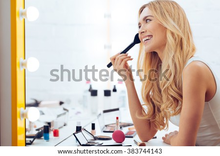 Adding some color to my cheeks. Side view of cheerful young womanapplying make-up and looking at her reflection in mirror while sitting at the dressing table - stock photo