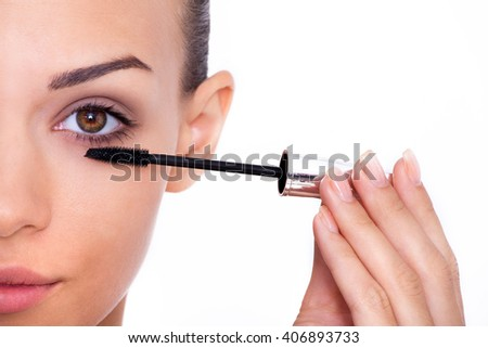 Adding some length to her lashes. Cropped shot of a beautiful young woman applying mascara to her lashes - stock photo