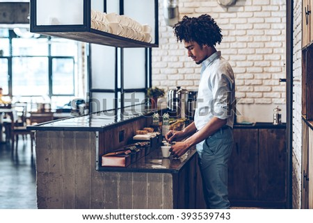 Adding some sugar. Side view of young African man stirring coffee while standing at bar counter - stock photo