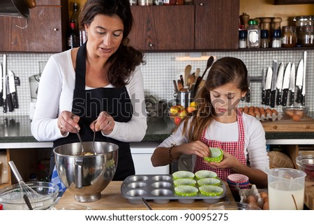 Adding the dough into the cupcake papers - stock photo