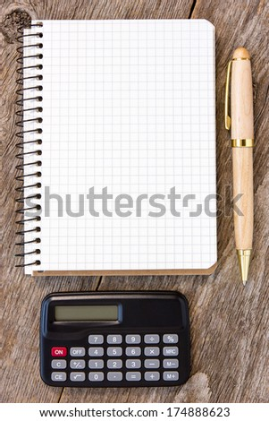 Adding up figures concept with calculator, pen and notebook on the wooden background - stock photo