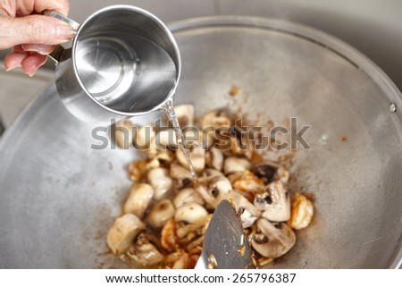 Adding water to the wok - stock photo