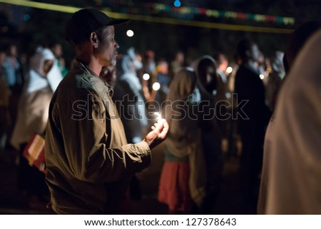 ADDIS ABABA, ETHIOPIA - JANUARY 19: A large crowd of people pray with candle light during Timket (baptism in Amharic) celebrations  on January 19, 2013 in Addis Ababa. - stock photo