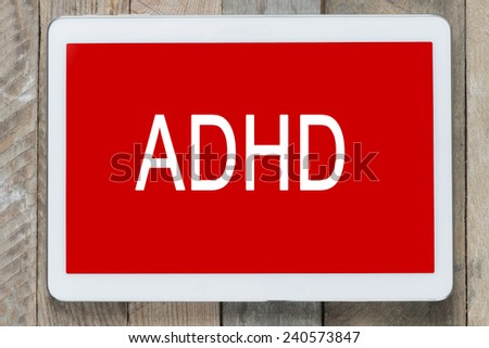ADHD word on tablet pc on wooden background  - stock photo