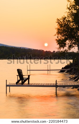 Adirondack chair on the end of a dock at sunset on Lake Willoughby, Vermont, USA - stock photo