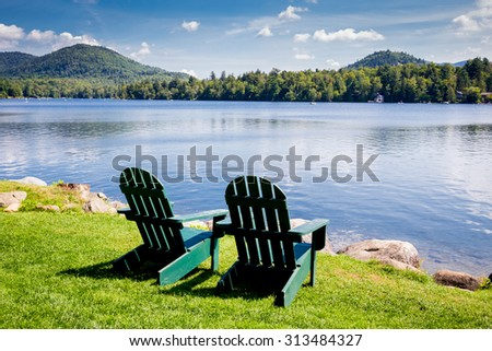 Adirondack chairs. Mirror Lake, Lake Placid New York. Summer, vacation, outdoors, travel, explore, nature, camping, lake and mountain vacation concept - stock photo