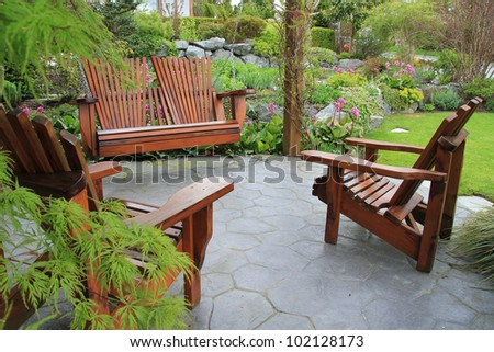 Adirondack wooden chairs on a patio in the garden. - stock photo