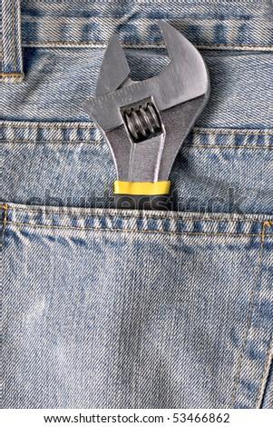 adjustable spanner in a blue jeans pocket - stock photo
