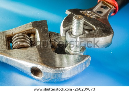 Adjustable wrench and bolt with nuts. - stock photo