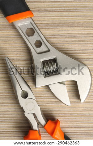 adjustable wrench and pliers closeup on wooden background.Extreme  close up - stock photo