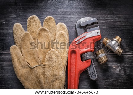 Adjustable wrench plumbing fittings leather protective gloves on wooden board. - stock photo