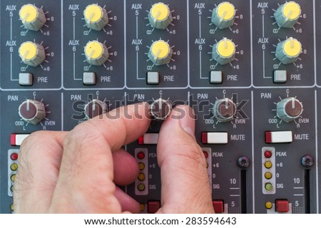 Adjusting audio sound mixer with buttons and sliders - stock photo