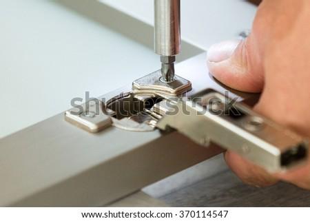 Adjusting / fixing cabinet door hinge - stock photo