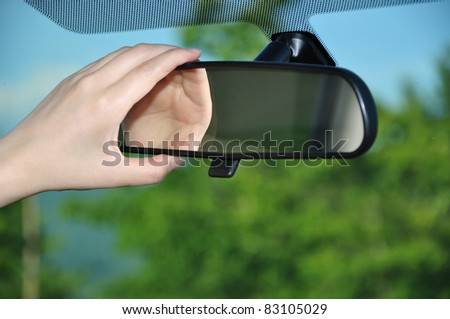 Adjusting rear view mirror - stock photo