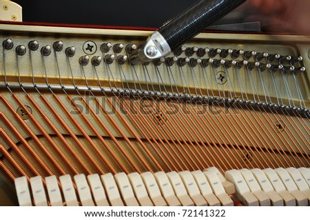 Adjusting the strings tension with a tool - stock photo