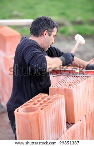 Adjusting wall with wooden mallet - stock photo