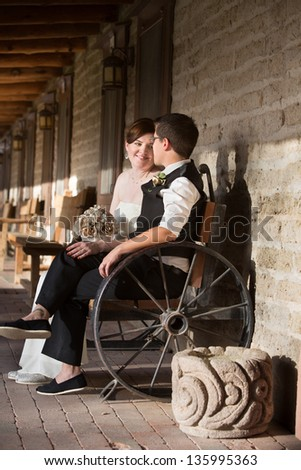 Admiring young lesbian married couple sitting outdoors - stock photo