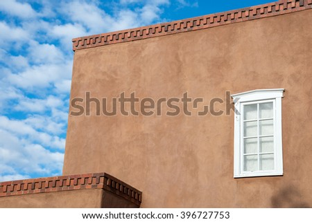 Adobe exterior accented with a single white window in Santa Fe, New Mexico - stock photo