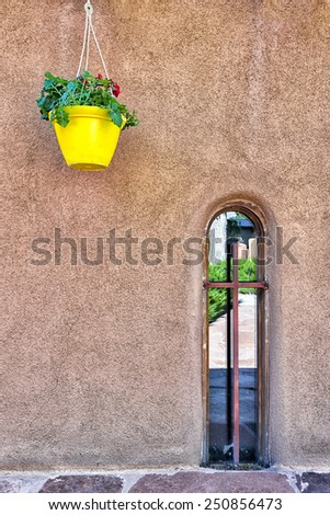 Adobe wall featuring a hanging yellow flower pot and an antique window frame - stock photo