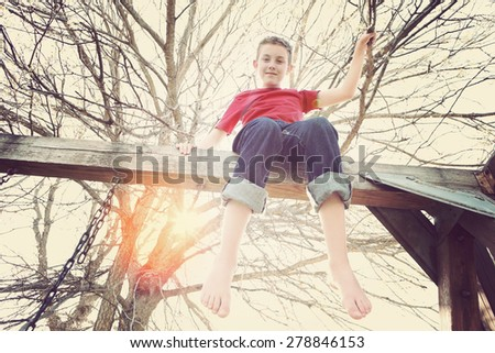 Adolescent boy sitting on top of a playground swing set. - stock photo