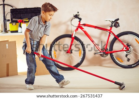 Adolescent boy with mop cleaning floor in garage - stock photo