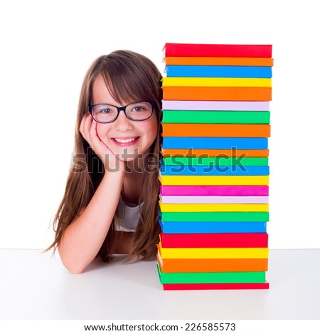 Adolescent girl smiling next to bunch of colorful books - stock photo