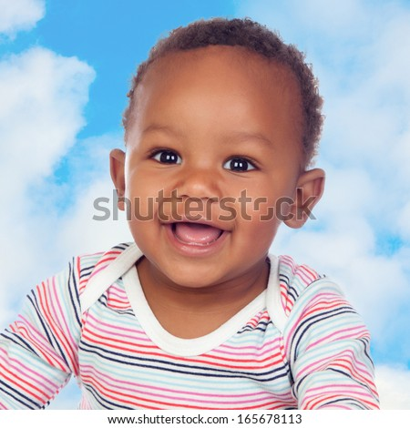 Adorable african baby smiling with a blue sky of background - stock photo