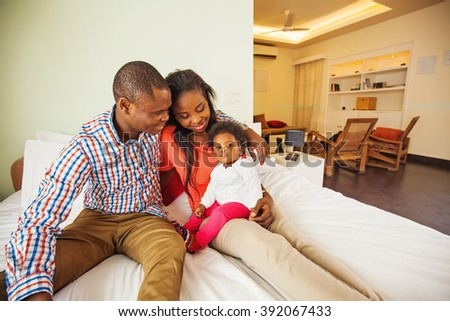 adorable african family at home looking at their baby - stock photo