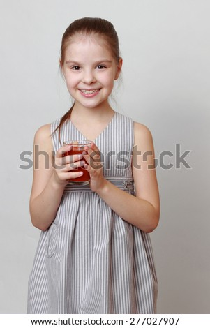Adorable and cheerful little girl holding tomato juice in glass - stock photo