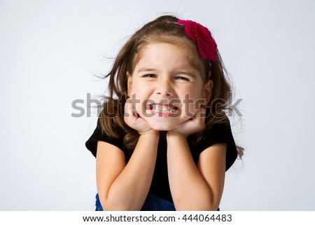 Adorable and expressive girl gritting her teeth and scrunching her face in a silly grin. - stock photo