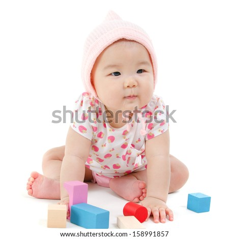 Adorable Asian baby girl playing wood blocks on floor, sitting isolated on white background. - stock photo