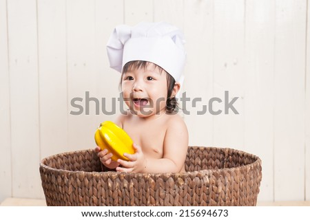 Adorable asian baby girl wearing a chef hat. Child sitting in the basket. White wooden background - stock photo