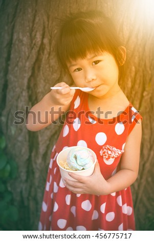 Adorable asian girl eating ice cream in the summer on vacation over a trunk of a tree background with bright sunlight. Pretty child enjoy and relax in nature. Outdoors.  Warm tone. - stock photo