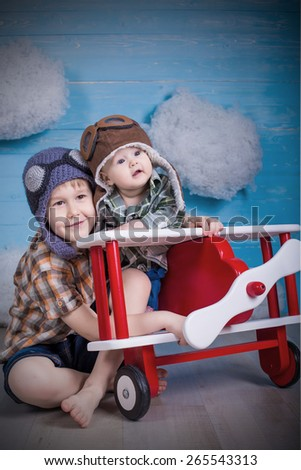 adorable babies brother and sister hugging each other in toy airplane on wooden background true emotions and feelings - stock photo