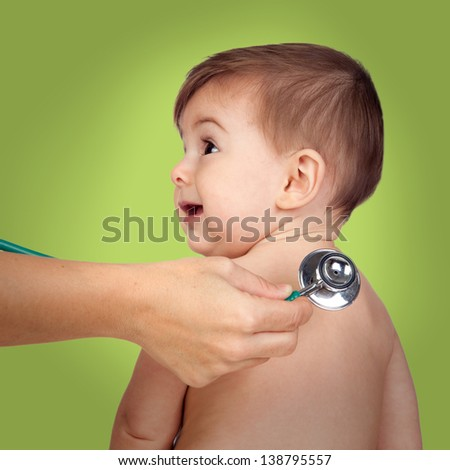 Adorable baby at the doctor's office for a pediatric examination on a green background - stock photo