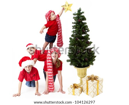 Adorable baby balancing precariously on her siblings backs as she places a star upon the Christmas tree - stock photo