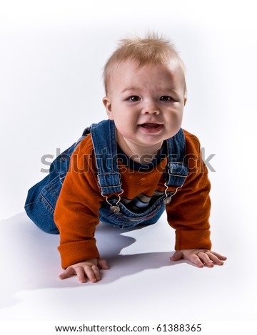 Adorable baby boy crawling toward the viewer wearing an orange shirt and overalls - stock photo