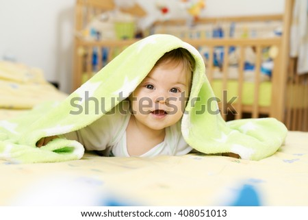 Adorable baby boy enjoying under his green blanket, looking at camera. - stock photo