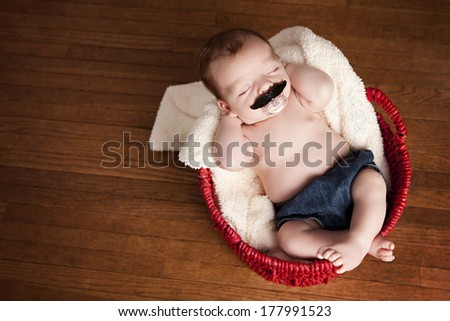 Adorable baby boy in a basket.  Room for your text. - stock photo