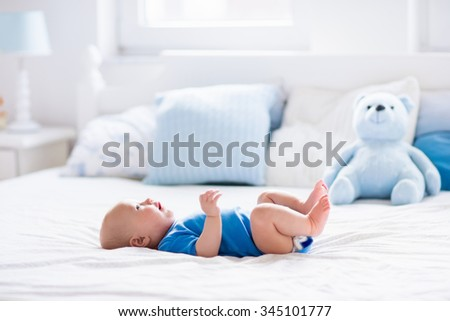 Adorable baby boy in white sunny bedroom. Newborn child relaxing in bed. Nursery for young children. Textile and bedding for kids. Family morning at home. New born kid during tummy time with toy bear. - stock photo