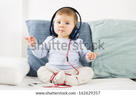 Adorable baby boy listening music at earphones while holding his hands in the air like a conductor. - stock photo