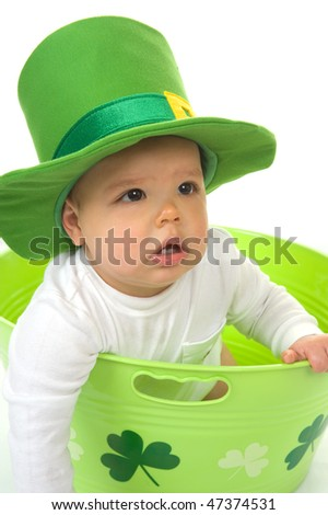 Adorable baby boy sitting in shamrock bucket wearing a St. Patrick's Day hat - stock photo