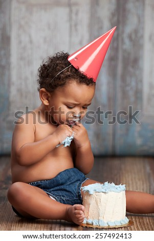 Adorable baby boy, sitting on a wood floor, wearing a party hat and eating a small cake.   - stock photo