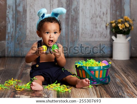Adorable baby boy sitting on the floor playing with plastic Easter Eggs and wearing bunny ears.   - stock photo