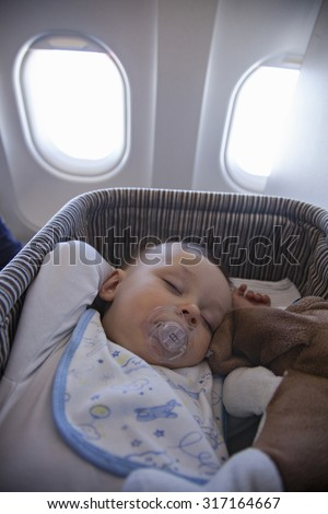 Adorable Baby Boy Sleeping In Special Bassinet On Airplane - stock photo