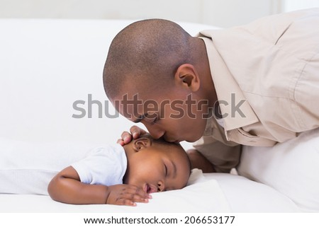 Adorable baby boy sleeping while being watched by father at home in the living room - stock photo